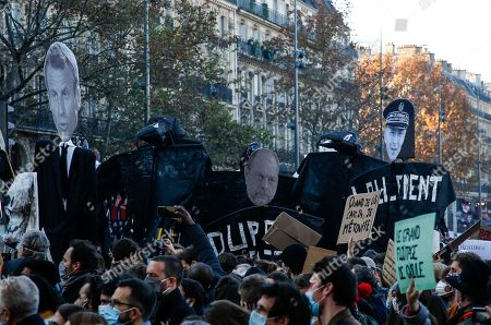 Demonstrators hold effigies of French President Emmanuel Macron, French Justice Minister Eric Dupont-Moretti and Paris police prefect Didier Lallement durind a protest against the newly passed controversial global security law, in Paris, France, 28 November 2020. The global security legislation passed by the French Parliament aims to ban the distribution of photos in which police officers and gendarmes can be identified in a way which is harmful to their image.