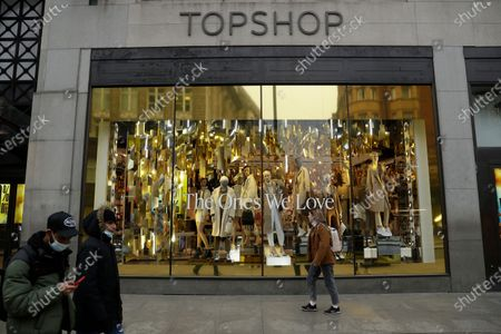 People wearing face masks to try to curb the spread of coronavirus walk past the temporarily closed Topshop flagship store on Oxford Street, during England's second coronavirus lockdown, in London, . Arcadia Group, the retail empire of tycoon Philip Green, which owns well-known British fashion chains like Topshop and employs around 15,000 people, appears to be on the brink of collapse following the economic shock of the coronavirus pandemic