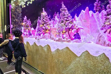 A little girl looking at a Christmas window. Atmosphere on Sunday evening in front of the Christmas windows at the department store, Le Bon Marche