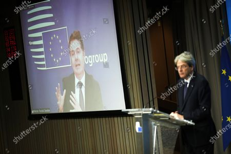 Eurogroup president Paschal Donohoe, on the screen, speaks next to European Commissioner for Economy Paolo Gentiloni during an online news conference following an Eurogroup video conference meeting at the European Council headquarters in Brussels