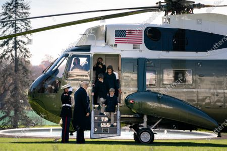 President Donald Trump, joined by grandchildren Arabella Kushner, Theodore Kushner and Joseph Kushner, disembark Marine One on the South Lawn of the White House Sunday, Nov. 29, 2020, returning from Camp David near Thurmont, Md.