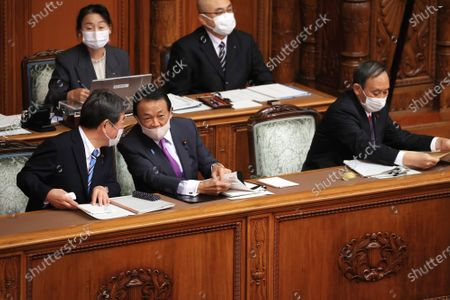 Japanese Finance Minister Taro Aso (2nd L) chats with Foreign Minister Toshimitsu Motegi (L) while Prime Minister Yoshihide Suga (R) listesn to a qustion at Upper House's plenary session at the National Diet in Tokyo on Monday, November 30, 2020.