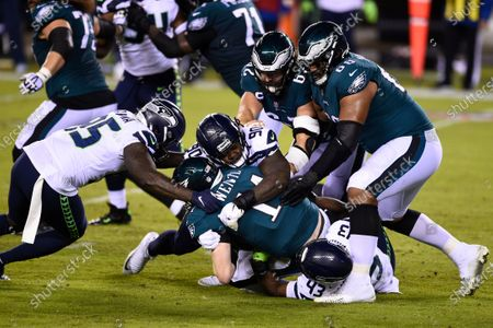 Stock Photo of Philadelphia Eagles' Carson Wentz (11) is tackled by Seattle Seahawks' Carlos Dunlap (43), Jarran Reed (90) and Benson Mayowa (95) during the first half of an NFL football game, in Philadelphia