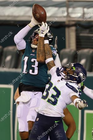 Philadelphia Eagles' Travis Fulgham (13) catches but can't control the ball in the end zone as Seattle Seahawks' Jamal Adams (33) defends. The tip was caught by the Eagles' Richard Rodgers (85) for a 33 yard touchdown catch with 12 seconds remaining in an NFL football game, in Philadelphia. The Seahawks defeated the Eagles