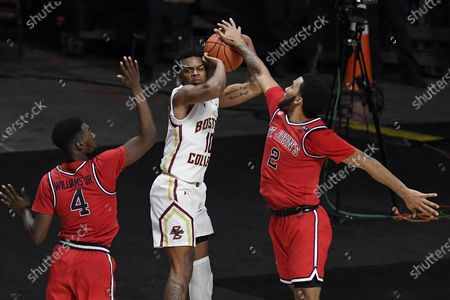 St. John's Julian Champagnie, right, stops a shot-attempt by Boston College's Wynston Tabbs, center, as St. John's Greg Williams Jr., left, defends in the second half of an NCAA college basketball game, in Uncasville, Conn