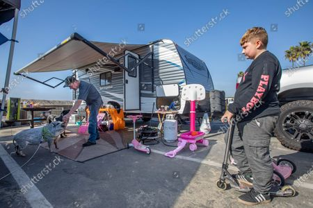 Cooper Wilson, right, looks on as Bill Lancaster of Oakley, Ca. feeds carrots to his pot bellied pig, Charlie, outside his RV camper at Dockweiler Rv Park in Playa del Rey. (Mel Melcon / Los Angeles Times)