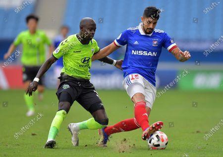 Thiago Martins (R) of Yokohama in action against Modou Barrow (L) of Jeonbuk during the AFC Champions League group H match between Yokohama Marinos and Jeonbuk Hyundai Motors at the Al-Janoub Stadium in Al-Wakrah, Qatar, 01 December 2020.