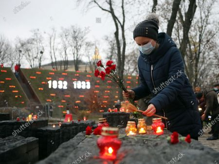 A woman lays wheat ears in memory of the victims of the 1932-1933 famine on the premises of the National Museum of the Holodomor-Genocide on the Holodomor Victims Remembrance Day, Kyiv, capital of Ukraine.