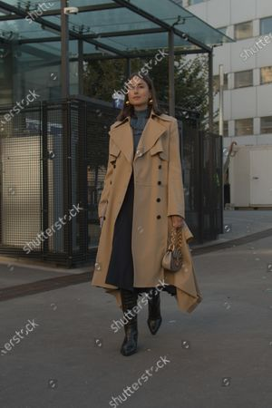 Julia Haghjoo wears a metallic turtleneck sweater, a grey skirt with stripes, a camel trench coat, leather boots and a bag by Chloé outside the Chloé show during Paris Fashion Week Womenswear Spring/Summer 2019