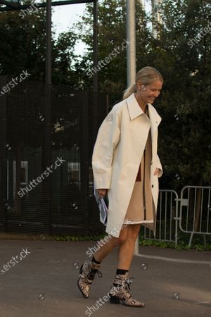 Holli Rogers wears a dress by Chloé, a white trench coat and animal print ankle boots outside the Chloé show during Paris Fashion Week Womenswear Spring/Summer 2019