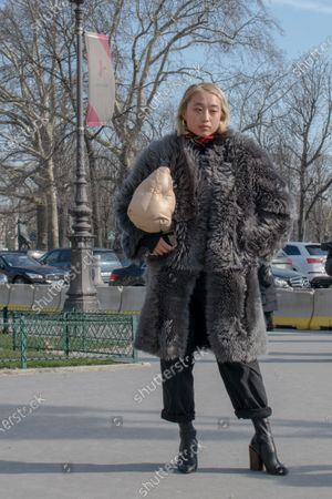 Margaret Zhang wears a grey fur coat, Baggy pants, high heels boots and a cream bag by Maison Margiela outside the Maison Margiela show during Paris Fashion Week Womenswear Fall Winter 2018