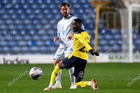 Stock Picture of Ipswich Town defender Luke Chambers (4) gets a pass away under pressure from Oxford United forward (on loan from QPR)  Olamide Shodipo (25) during the EFL Sky Bet League 1 match between Oxford United and Ipswich Town at the Kassam Stadium, Oxford