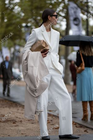 Stock Picture of Julie Pelipas wears a white suit, a beige leather coat and black loafers outside the Chanel show during Paris Fashion Week Womenswear Spring Summer 2020