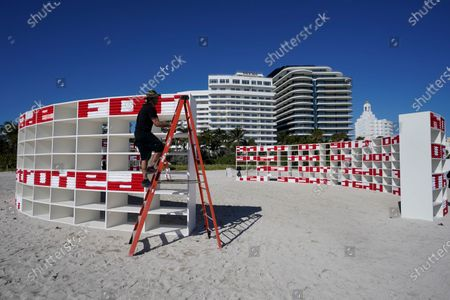 "Stock Picture of Marcos Barrera climbs a ladder as he performs maintenance on an outdoor artwork by Cuban artist Alexandre Arrechea titled 'DREAMING WITH LIONS,', in Miami Beach, Fla. The installation, which has phrases from Ernest Hemingway's ""The Old Man and the Sea,"" was part of Miami Art Week"