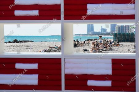 "Beachgoers are seen through holes of an outdoor artwork by Cuban artist Alexandre Arrechea titled 'DREAMING WITH LIONS,', in Miami Beach, Fla. The installation, which has phrases from Ernest Hemingway's ""The Old Man and the Sea,"" was part of Miami Art Week"