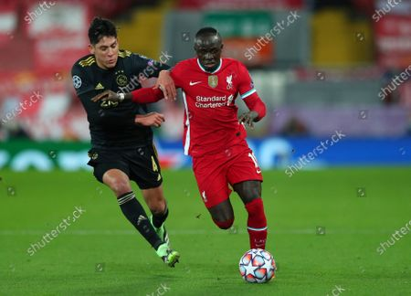 Liverpool's Sadio Mane, right, duels for the ball with Ajax's Edson Alvarez during the Champions League group D soccer match between Liverpool and Ajax at Anfield stadium in Liverpool, England