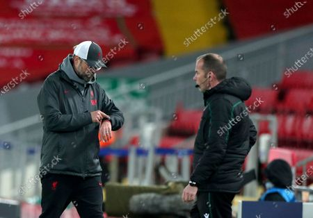 Liverpool's manager Jurgen Klopp, left, check his watch during the Champions League group D soccer match between Liverpool and Ajax at Anfield stadium in Liverpool, England
