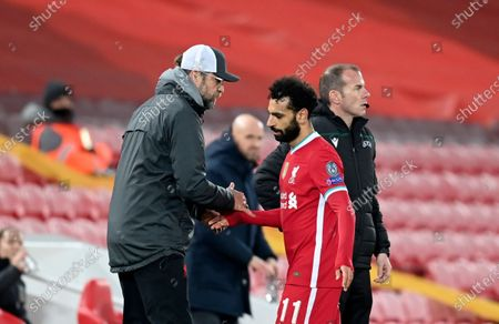 Liverpool's manager Jurgen Klopp, left, shakes hands with Liverpool's Mohamed Salah during the Champions League group D soccer match between Liverpool and Ajax at Anfield stadium in Liverpool, England