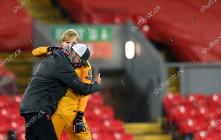 Liverpool's manager Jurgen Klopp, left, celebrates with Liverpool's goalkeeper Caoimhin Kelleher at the end of the Champions League group D soccer match between Liverpool and Ajax at Anfield stadium in Liverpool, England