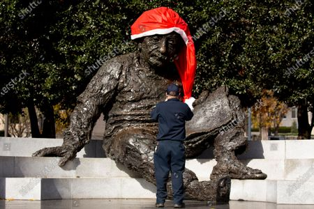 A man pauses by the Albert Einstein Memorial, currently decorated with a Santa hat, in Washington, DC, USA, 01 December 2020. The United States has entered the holiday season as coronavirus COVID-19 new cases and hospitalizations are surging.
