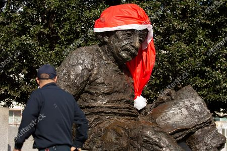 Stock Photo of A man pauses by the Albert Einstein Memorial, currently decorated with a Santa hat, in Washington, DC, USA, 01 December 2020. The United States has entered the holiday season as coronavirus COVID-19 new cases and hospitalizations are surging.