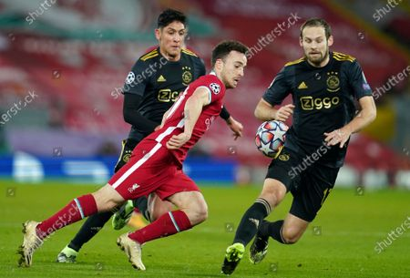 Stock Photo of Ajax's Edson Alvarez, left, and Ajax's Daley Blind, right, challenge Liverpool's Diogo Jota during the Champions League group D soccer match between Liverpool and Ajax at Anfield stadium in Liverpool, England