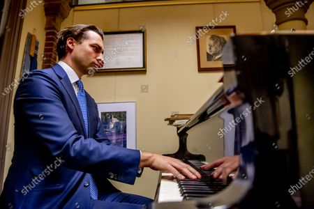 Thierry Baudet playing on a piano fvd (Forum for Democracy) and freek jansen after question time in the House of Representatives in their party office in the second room