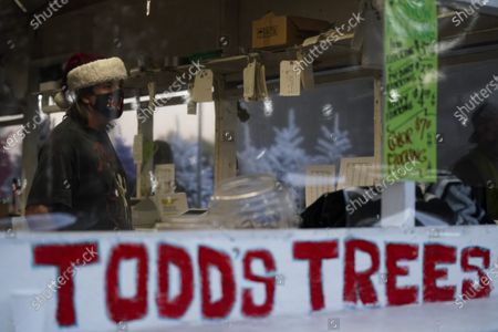 Stock Picture of Mike Todd wears a mask while standing inside a checkout booth covered in plastic at his family's Christmas tree stand, in Long Beach, Calif