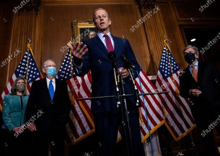 United States Senator John Thune (Republican of South Dakota), center, speaks with reporters following the weekly US Senate Republican Conference meeting in the Mansfield Room of the US Capitol in Washington, DC. Looking on from behind Sen. Thune, from left to right: US Senator Joni Ernst (Republican of Iowa), US Senate Majority Leader Mitch McConnell (Republican of Kentucky), and US Senator Roy Blunt (Republican of Missouri)