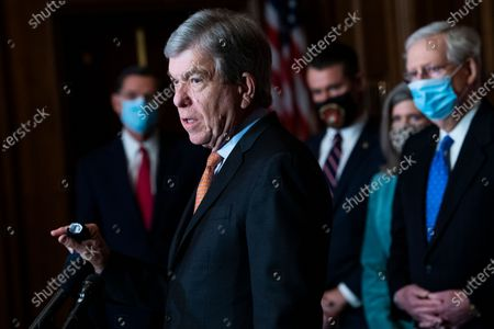 United States Senator Roy Blunt (Republican of Missouri) speaks with reporters following the weekly US Senate Republican Conference meeting in the Mansfield Room of the US Capitol in Washington, DC. In the background from left, US Senator John Barrasso (Republican of Wyoming), US Senator Todd Young (Republican of Indiana), US Senator Joni Ernst (Republican of Iowa), and US Senate Majority Leader Mitch McConnell (Republican of Kentucky), also appear.