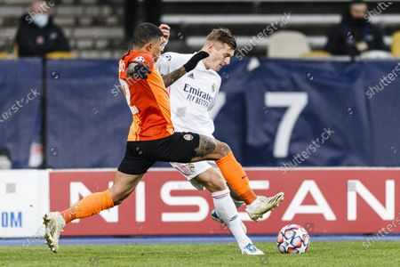 Dodo Santos of Shakhtar (L) fights for the ball with Toni Kroos of Real Madrid (R)