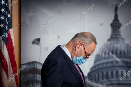 Senate Minority Leader Chuck Schumer, D-NY, listens while United States Senator Bob Menendez (Democrat of New Jersey) offers remarks during a press conference at the US Capitol in Washington, DC.,.