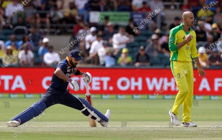 India's Virat Kohli, left, stretches his legs while batting against Australia's Ashton Agar, right, during their one day international cricket match at Manuka Oval in Canberra, Australia