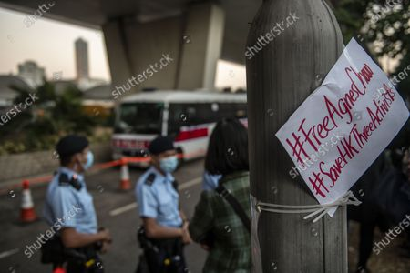 Stock Photo of A Placard is seen next to police officers standing guard outside the courthouse on December 2, 2020 in Hong Kong, China. Chow, Wong and Lam were sentenced to 10 months, 13.5 months and 7 months respectively behind bars for their roles in an anti-government protest in 2019.