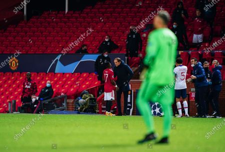 Fred of Manchester United talks to Paris Saint-Germain manager Thomas Tuchel after he was sent off with a red card following two yellow cards