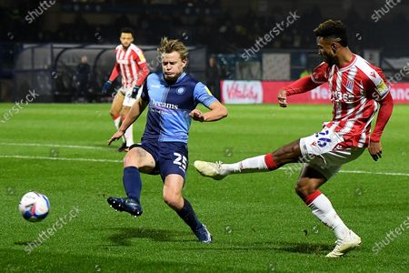 Stoke City forward Tyrese Campbell (26) crosses the ball under pressure from Wycombe Wanderers striker Alex Samuel (25) during the EFL Sky Bet Championship match between Wycombe Wanderers and Stoke City at Adams Park, High Wycombe