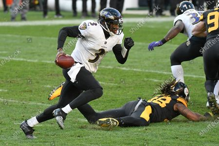 Baltimore Ravens quarterback Robert Griffin III (3) scrambles past Pittsburgh Steelers outside linebacker Bud Dupree (48) during the first half of an NFL football game, in Pittsburgh
