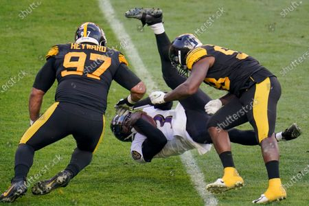 Baltimore Ravens quarterback Robert Griffin III (3) flies as he is tripped up as he scrambles past Pittsburgh Steelers defensive end Cameron Heyward (97) and inside linebacker Vince Williams (98) in the first half during an NFL football game, in Pittsburgh