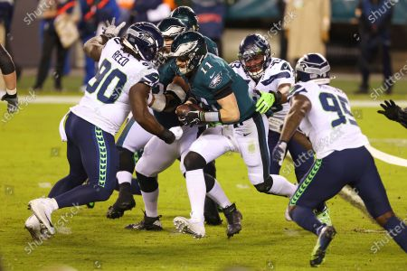 Philadelphia Eagles' Carson Wentz (11) attempts to get past Seattle Seahawks' Jarran Reed (90), Carlos Dunlap (43) and Benson Mayowa (95) during an NFL football game, in Philadelphia. The Seahawks defeated the Eagles