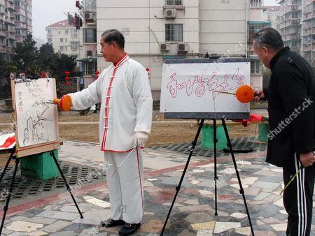 Yang Zhibiao (L) and Wen Kaibian demonstrate their yo-yo calligraphy