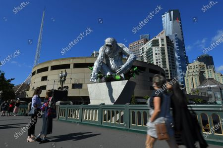 People observe a large-scale sculpture of chimpanzee David Greybeard, unveiled as part of a collaboration between Australian visual artist Lisa Roet and wildlife conservation organisation the Jane Goodall Institute Global, outside Hamer Hall in Melbourne, Australia, 03 December 2020.