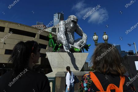People observe a large-scale sculpture of chimpanzee David Greybeard, unveiled as part of a collaboration between Australian visual artist Lisa Roet and wildlife conservation organisation the Jane Goodall Institute Global, outside Hamer Hallin Melbourne, Australia, 03 December 2020.