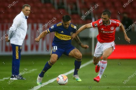Eduardo Salvio of Argentina's Boca Juniors, left, and Uendel of Brazil's Internacional battle for the ball during a Copa Libertadores round of sixteen first leg soccer match at the Beira-Rio stadium in Porto Alegre, Brazil
