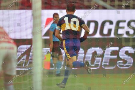 Stock Image of Wearing the number 10 jersey that Diego Maradona used playing for Boca Junior's Carlos Tevez celebrates scoring his side's opening goal against Brazil's Internacional during a Copa Libertadores round of sixteen first leg soccer match at the Beira-Rio stadium in Porto Alegre, Brazil