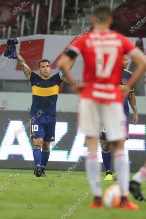 Wearing the number 10 jersey that the late Diego Maradona used playing for Boca Junior's, striker Carlos Tevez celebrates scoring his side's opening goal against Brazil's Internacional during a Copa Libertadores round of sixteen first leg soccer match at the Beira-Rio stadium in Porto Alegre, Brazil