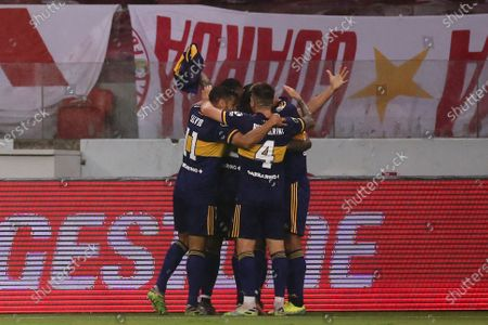 Teammates surround Boca Junior's Carlos Tevez after he scored his side's opening goal against Brazil's Internacional during a Copa Libertadores round of sixteen first leg soccer match at the Beira-Rio stadium in Porto Alegre, Brazil