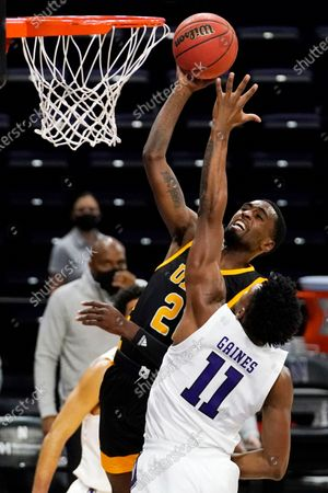 Arkansas-Pine Bluff guard Shaun Doss Jr., top, drives to the basket against Northwestern guard Anthony Gaines during the first half of an NCAA college basketball game in Evanston, Ill