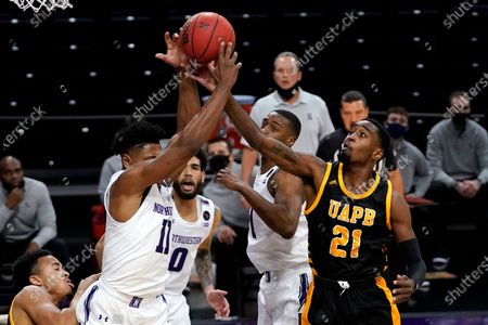 Arkansas-Pine Bluff guard Shaun Doss Jr., right, and Northwestern guard Anthony Gaines reach for a rebound during the first half of an NCAA college basketball game in Evanston, Ill