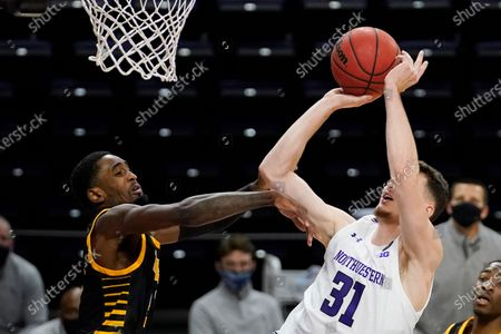 Northwestern forward Robbie Beran shoots next to Arkansas-Pine Bluff guard Shaun Doss Jr. during the second half of an NCAA college basketball game in Evanston, Ill