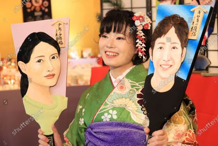 "Japanese doll maker Kyugetsu employee in kimono displays ornamental wooden rackets ""hagoita"" decorated with depiction of actress Satomi Ishihara (L) and young female swimmer Rikako Ikee (R) at the company's showroom in Tokyo on Thursday, December 3, 2020. The company made special hagoitas for this year's news makers as yearend tradition."